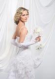 一件白色礼服的一个年轻和可爱的白肤金发的新娘 库存照片