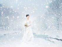 一件白色礼服的一个年轻深色的新娘在雪 免版税库存图片