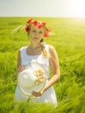 一件白色礼服的一名妇女在阳光下有鸦片花圈的在他的头的 免版税库存图片