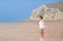 一件白色礼服的卷曲小女孩在异乎寻常的海滩 库存照片