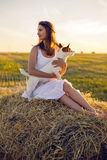 一件白色礼服的女孩与杰克罗素狗狗坐干草堆 免版税库存照片