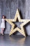一件白色礼服的女孩在星设施的背景 免版税库存照片