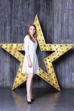 一件白色礼服的女孩在星设施的背景 库存图片