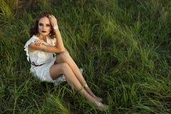 一件白色礼服的女孩坐草 免版税库存照片