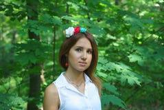 一件白色礼服的女孩有花一个手工制造花圈的  免版税库存照片