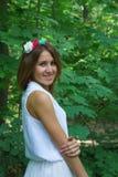一件白色礼服的女孩有花一个手工制造花圈的  库存照片