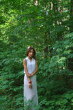 一件白色礼服的女孩有花一个手工制造花圈的  免版税图库摄影