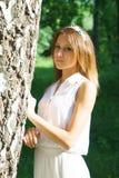 一件白色礼服的女孩有花一个手工制造花圈的  库存图片