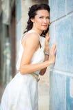 一件白色礼服的妇女在老石墙附近 库存照片