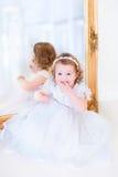 一件白色礼服的小女孩在镜子旁边 图库摄影
