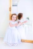 一件白色礼服的小女孩在镜子旁边 库存照片