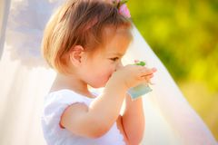 一件白色礼服的小美丽的女孩从杯子喝 免版税库存图片