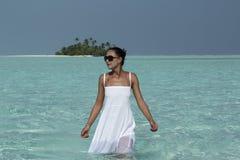 一件白色礼服的少妇走在turquise水马尔代夫中的 库存照片