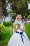 一件白色礼服的新娘在夏天有花束的绿色公园在手中 免版税图库摄影