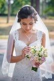 一件白色礼服的新娘在夏天有花束的绿色公园在手中 免版税库存图片