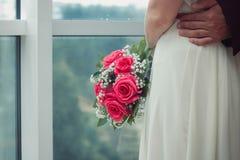 一件白色礼服的新娘拥抱她的丈夫,她站立在窗口 免版税库存照片