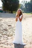 一件白色礼服的祈祷的女孩新娘在晴朗室外 免版税库存图片