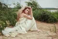 一件白色礼服的美丽的女孩坐海滩并且调查距离 免版税库存图片