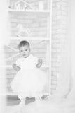 一件白色礼服的美丽的女婴在与基督的内部 免版税库存照片
