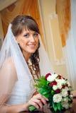一件白色礼服的美丽的愉快的新娘有婚礼花束的 库存照片