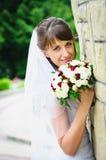 一件白色礼服的美丽的愉快的新娘有婚礼花束的 免版税库存照片