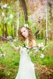 一件白色礼服的美丽的新娘在开花在春天从事园艺 库存图片