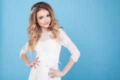 一件白色礼服的美丽的新娘在蓝色背景 库存图片