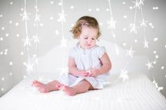 一件白色礼服的逗人喜爱的卷曲小孩女孩在圣诞灯之间的床上 免版税库存照片