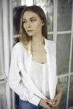 一件白色礼服的镇静美丽的少妇在家 免版税图库摄影