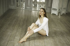 一件白色礼服的镇静美丽的少妇在家 免版税库存照片