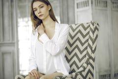 一件白色礼服的镇静美丽的少妇在家 图库摄影