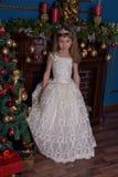 一件白色礼服的年轻公主有在她的头的一个冠状头饰的在圣诞树 免版税库存图片