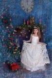 一件白色礼服的年轻公主有在她的头的一个冠状头饰的在圣诞树 免版税库存照片
