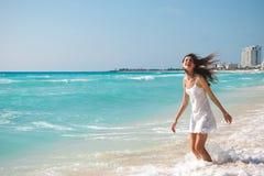 一件白色礼服的年轻美丽的妇女是停留和笑o 免版税库存图片