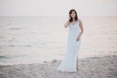 一件白色礼服的年轻美丽的妇女走在一个空的海滩的在海洋附近 库存图片