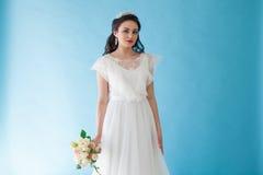 一件白色礼服的Bride公主有在蓝色背景的一个冠的 免版税库存图片