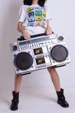 一件白色衬衣的亭亭玉立的女孩和黑鞋子拿着老磁带记录器 免版税库存图片