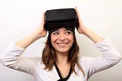 一件白色衬衣的好奇,微笑的妇女,离开或投入在Oculus裂口VR虚拟现实3D耳机 免版税库存图片