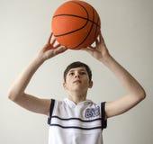 一件白色衬衣的少年男孩有篮球的一个球的 免版税库存图片