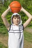 一件白色衬衣的少年男孩有篮球的一个球的 库存照片