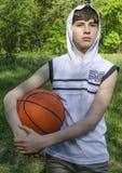 一件白色衬衣的少年男孩有篮球的一个球的 免版税图库摄影