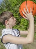 一件白色衬衣的少年男孩有篮球的一个球的 免版税库存照片