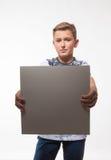 一件白色衬衣的情感白肤金发的男孩有一张灰色纸片的笔记的 库存照片