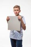 一件白色衬衣的情感白肤金发的男孩有一张灰色纸片的笔记的 图库摄影