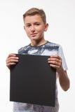 一件白色衬衣的情感白肤金发的男孩有一张灰色纸片的笔记的 免版税图库摄影