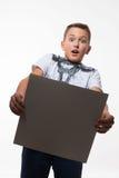 一件白色衬衣的情感白肤金发的男孩有一张灰色纸片的笔记的 免版税库存图片