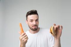 一件白色衬衣的有胡子的人在拿着汉堡包和红萝卜的轻的背景 免版税库存照片