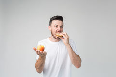一件白色衬衣的有胡子的人在拿着汉堡包和苹果的轻的背景 免版税库存图片
