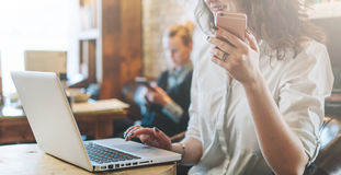 一件白色衬衣的年轻微笑的女商人坐在咖啡馆的桌上并且使用膝上型计算机,当拿着智能手机时 库存照片