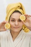 一件白色长袍的女孩举行柠檬的两个一半 库存图片